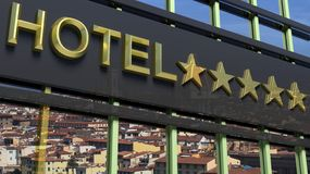 Big metallic glass hotel sign board with five golden stars Royalty Free Stock Photography