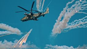 A big military combat green camouflage coloring helicopter spreads a smoke screen using smoke bombs - fireworks stock footage