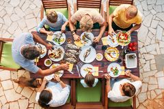 Big miltigeneration family dinner in process. Top view vertical image on table with food and hands royalty free stock photography