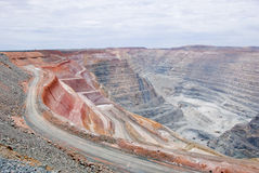 Big mine pit with little dump trucks and reddish soil Royalty Free Stock Photos