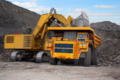Big mining truck and excavator. A picture of a big yellow mining truck at worksite Royalty Free Stock Photo