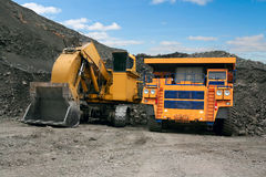 Big mining truck and excavator. A picture of a big yellow mining truck at worksite Royalty Free Stock Photos