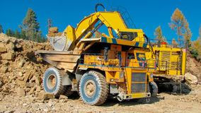 Big mining truck and excavator. A picture of a big yellow mining truck at worksite Royalty Free Stock Image