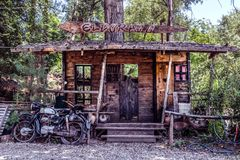 Big model of wild west saloon and old motorcycle royalty free stock photo