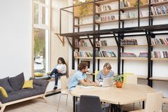 Big modern library in morning. Two people sitting, looking in laptop monitor talking about startup project. Girl sitting. On window sill reading book on Stock Photography
