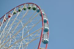 Big and modern multicolour ferris wheel on clean blue sky background.  stock photos