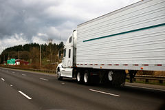 Big modern white semi truck trailer reefer on wide highway Stock Photos