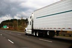 Big modern white semi truck trailer reefer on wide highway Stock Photos