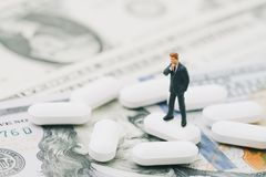 Big money in health care and medical industry business concept,. Miniature businessman thinking and standing on white tablet pills on US dollar banknotes Stock Image