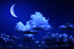Big moon and stars in a cloudy night blue sky Royalty Free Stock Image