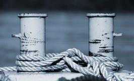 Big mooring bollard with nautical ropes, blue toned Stock Photos