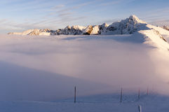 Big mountain peaks at sunset and inversion Stock Images