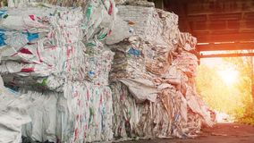 Big mountains of pressed trash against the backdrop of a sunset, recycling, polluted royalty free stock photography