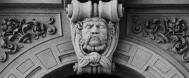 Big moustache male face on the main door. Shot in black and white, detail on the sculpture on the facade of this historic building representing some characters Royalty Free Stock Images