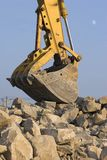 Big Mouth. Large Excavator jaws resting on rock pile Royalty Free Stock Images