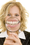 Big mouth. Laughing business woman holding a magnifying glass in front of her mouth Royalty Free Stock Photos