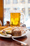 Big mug of beer and cold dishes on a little table Stock Images