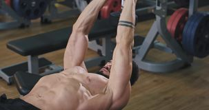 The big muscular man looks very concentrated while working out, he is in a bright gym and it looks very neat and clean.  stock video