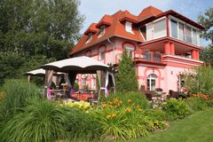 Big new house with nice garden. New, light pink colored house (use as a hotel) with very nice garden. Flowers and pavilions in the garden Stock Images