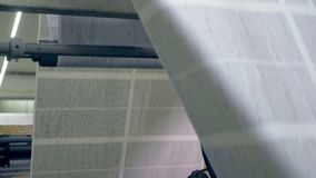 Big newspaper sheet rollling on a conveyor, close up. Newspaper sheet moving on a roll conveyor
