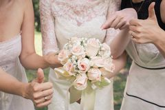 Big nice wedding bouquet in woman`s hands. Bride and bridesmaids show sign OK and thumbs up.  royalty free stock photo