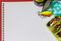 Big notebook with fishing tackles on color paper background Stock Photo