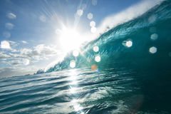 Big ocean wave in beautiful light. Surfing wave with bright sun and light bokeh on water drops Stock Photos