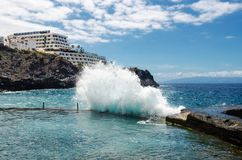 Big ocean wave breaking on natural swimming pool in town Los Gigantes `Cliffs of the Giants`. Canary Islands, Tenerife, Spain. Royalty Free Stock Images