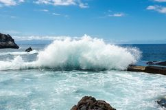 Big ocean wave breaking on natural swimming pool in town Los Gigantes `Cliffs of the Giants`. Canary Islands, Tenerife, Spain. Royalty Free Stock Photography