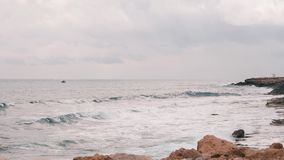 Big ocean waves crashing on rocky beach. Beautiful view of Mediterranean sea with rocky beach. Windy stormy ocean with big waves. Big stormy waves sway a small stock footage
