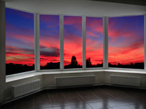 Big office windows with sunset beyond it Stock Images