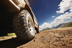 Big offroad car wheel on country road. Bottom view to big offroad car wheel on country road and mountains backdrop. Space for text royalty free stock photo