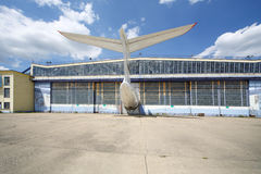 Big old battered aircraft hanger with protruding tail of plane. At sunny summer day stock photo