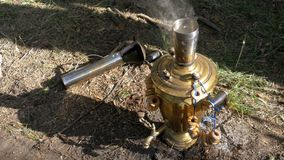 Big old Bronze samovar stands on the ground and prepares tea. stock video