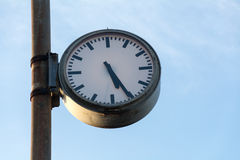 Big old clock at a rusty pole against the blue sky Royalty Free Stock Photography