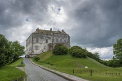 Big old dark ancient castle on the hill in the village not far from Lviv city. In Ukraine Stock Photography
