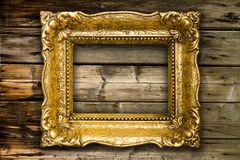Old Gold Picture Frame on wooden background royalty free stock photo