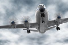 Big old propeller airplane. Old aircraft flying towards the camera; the worm's-eye view and dark clouds create a slightly ominous atmosphere stock photos