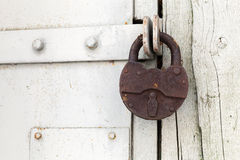 Big old rusted padlock hanging on the door Stock Images