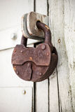 Big old rusted padlock hanging on rural door Royalty Free Stock Photos