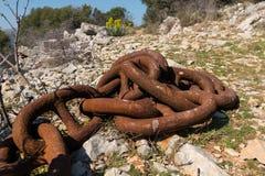 Big old rusty anchor chain lying on the ground. Croatia Stock Image