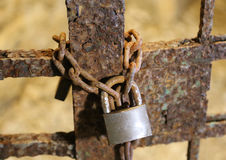Big old rusty padlock with the chain and the closed gate Royalty Free Stock Photography