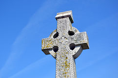 Big old stone celtic cross and blue sky Stock Photography