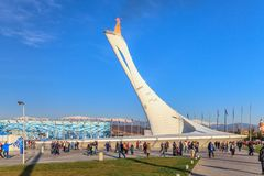 Big Olympic Torch erection with burning flame in Olympic Park was main venue of Sochi Winter Olympics in 2014. People chill out on. Sochi, Russia - February 15 royalty free stock image