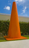 Big Orange Cone. A peculiarly large orange cone situated beside a wall royalty free stock photo