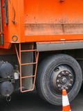 Big orange dump truck detail with tire. And safety cone Stock Image