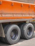 Big orange dump truck. Side panel with 4 tires Royalty Free Stock Photo