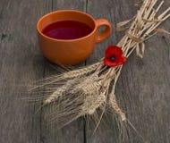 Big orange mug of juice and stalks of wheat Stock Images