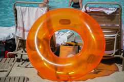 Big Orange Plastic Inner Tube Poolside with Deck Chairs in Sun. Large round plastic orange inner tube for pool play sits  on the side of the pool propped up with Stock Photos
