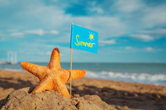 Big orange starfish with flag at the seashore Stock Photo